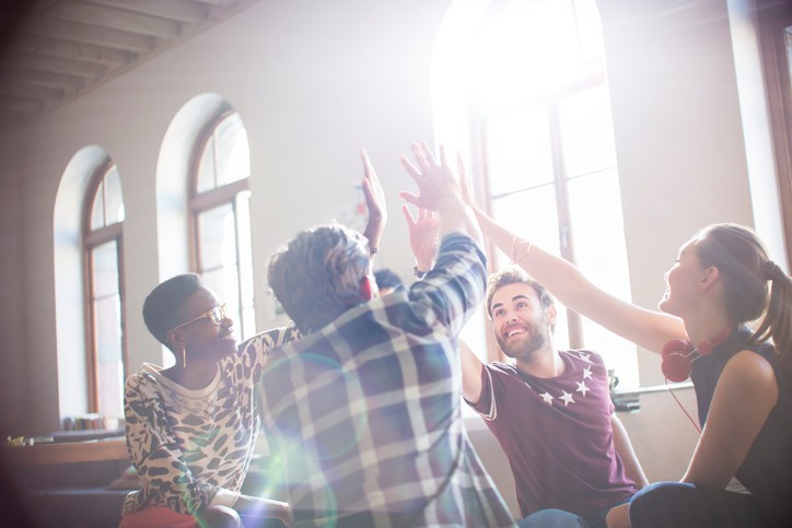 Casual business people raising hands in circle in sunny office meeting