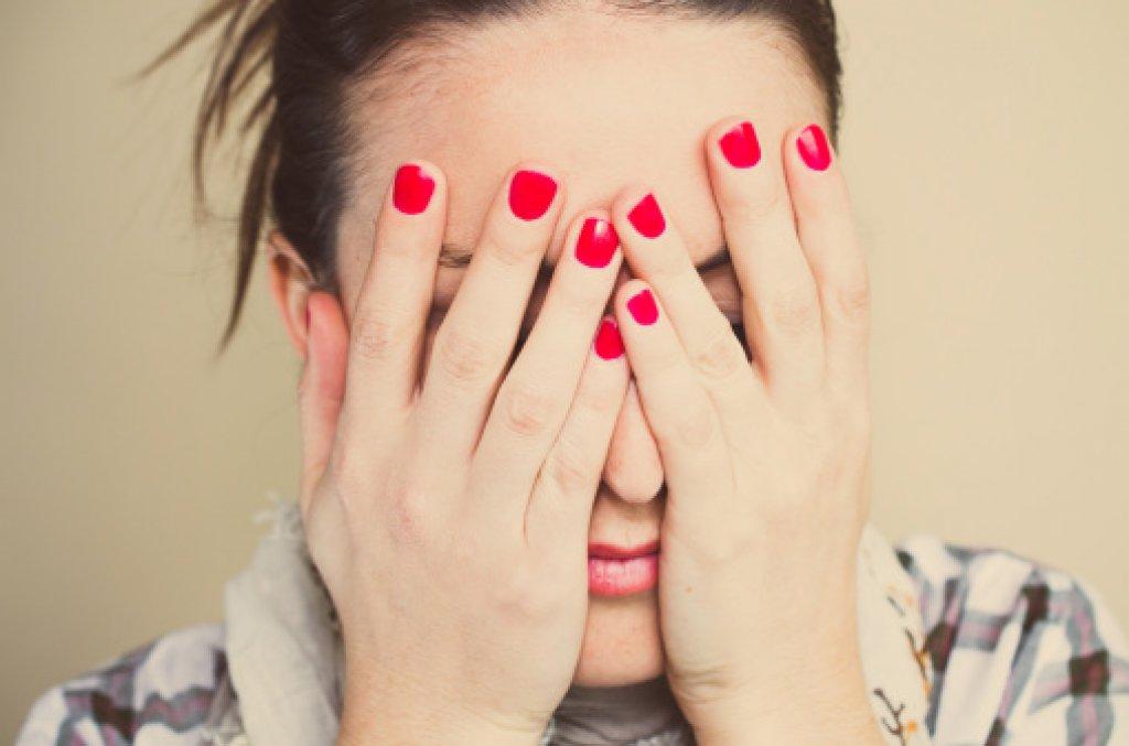 Nervös, orolig kvinna händerna för ansiktet