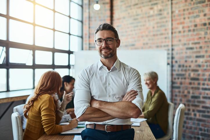 En man som är ny chef i kontorsmiljö står med korslagda armar och ler in i kameran.
