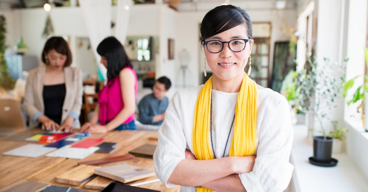 En kvinna i förgrunden som tittar in i kameran medan hennes projektdeltagare jobbar i bakgrunden – Framfot företagsutbildning