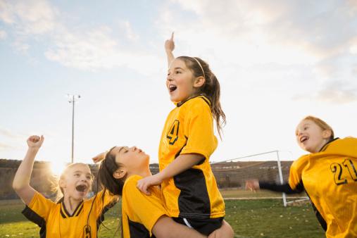Glada fotbollstjejer på fotbollsplanen firar framgång som team. | Framfot