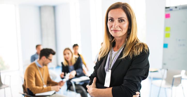 En kvinna som är ledare eller chef på sin arbetsplats md teamet i bakgrunden – Framfot företagsutbildning.