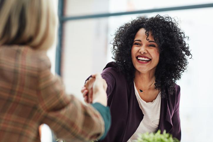 Framfot företagsutbildning–Två kollegor skakar hand under ett arbetsmöte.