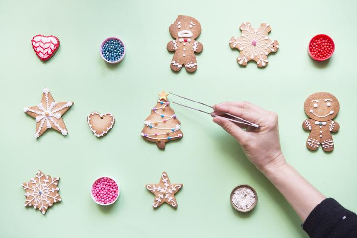 En kvinnas hand som dekorerar kakor med hjälp av pincett för att det ska bli perfekt – Framfot företagsutbildning