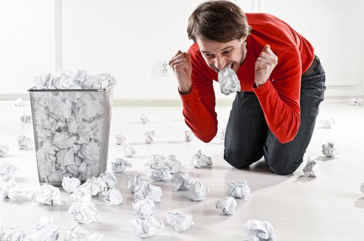 Man som uttrycker kreativ, perfektionistisk frustration på golvet bredvid en papperskorg full med hopskrynklade papper – Framfot företagsutbildning.