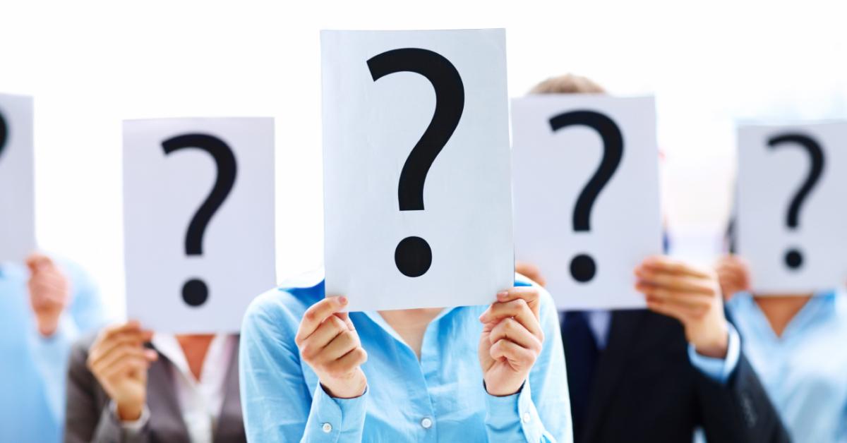 En grupp med personer som håller skyltar med frågetecken framför sina ansikten – Framfot företagsutbildning.