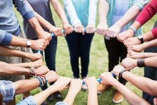 Grupp i cirkel med händer runt en rockring