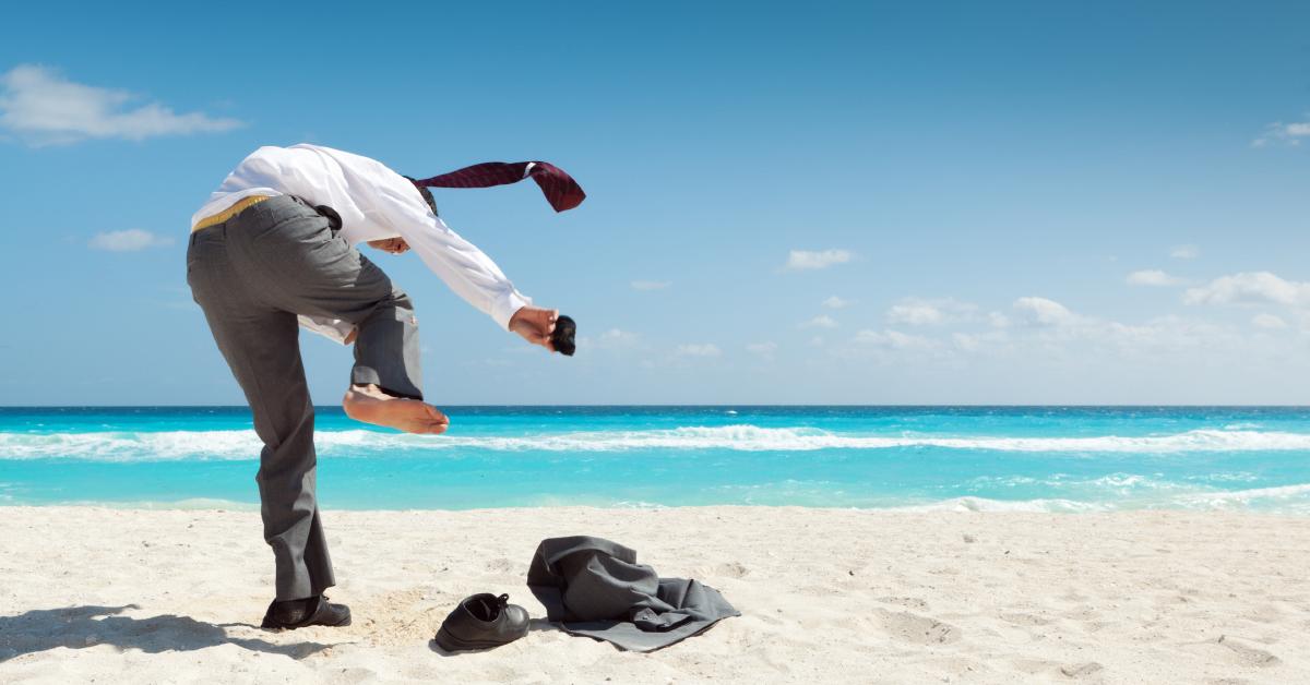 Bild av en sandstrand med en man som skyndsamt drar av sig kostymen för att springa i vattnet. - Framfot företagsutbildning