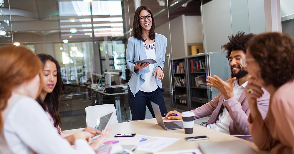 Kvinnlig ledare med medarbetare har roligt på mötet. | Framfot företagsutbildning