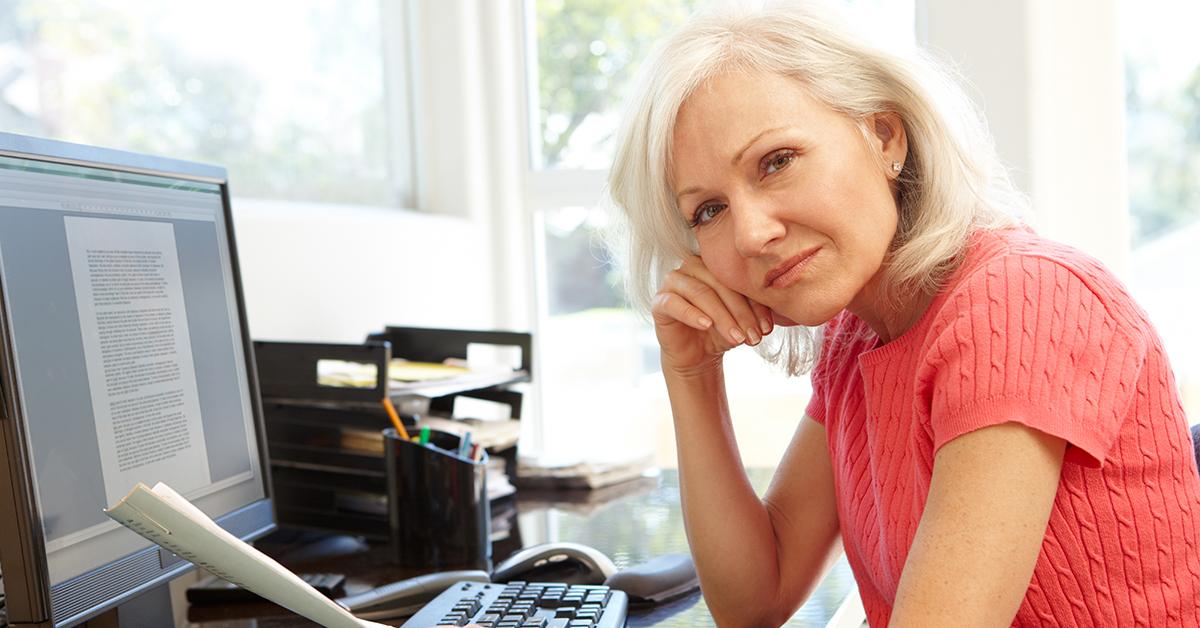 Kvinna på sin arbetsplats som chef sitter framför datorn och tittar uppgivet in i kameran.