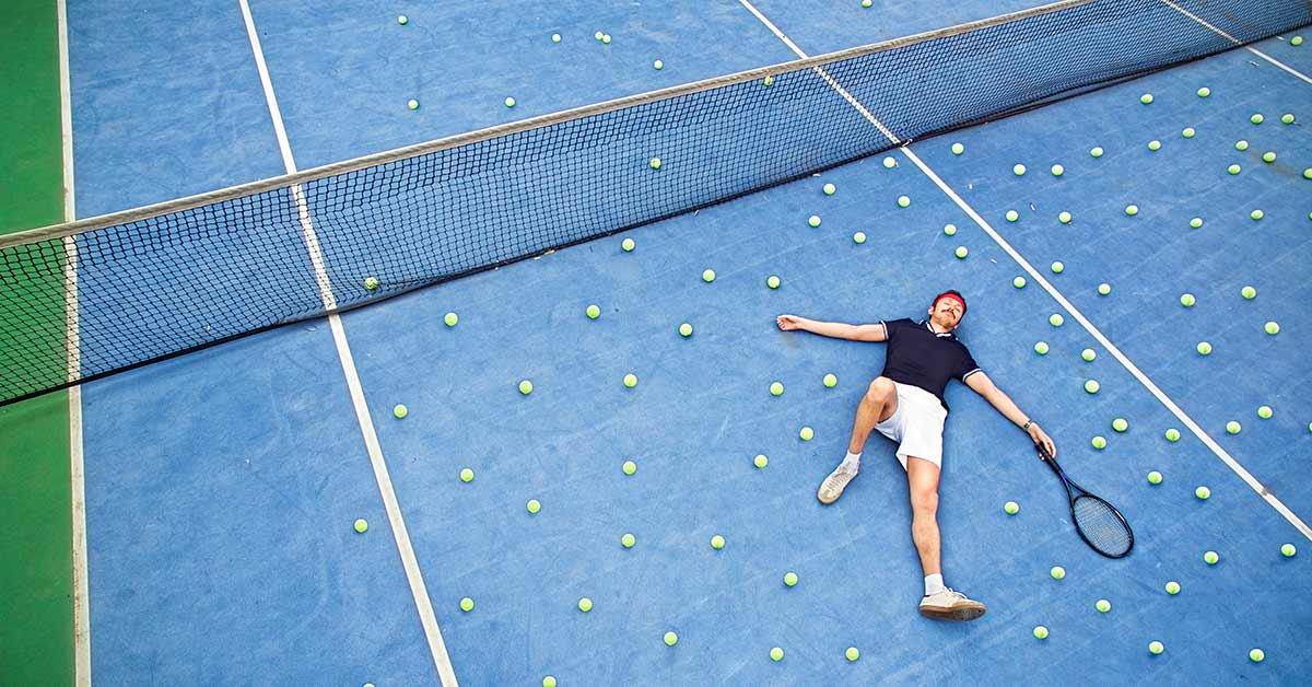 Liggande man som tappat många bollar på tennisplanen