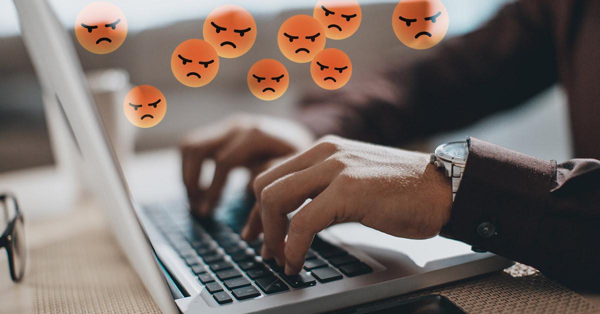 Närbild på händer som skriver på ett tangentbord med arga emojis ovanför som symbol för näthat – Framfot företagsutbildning.