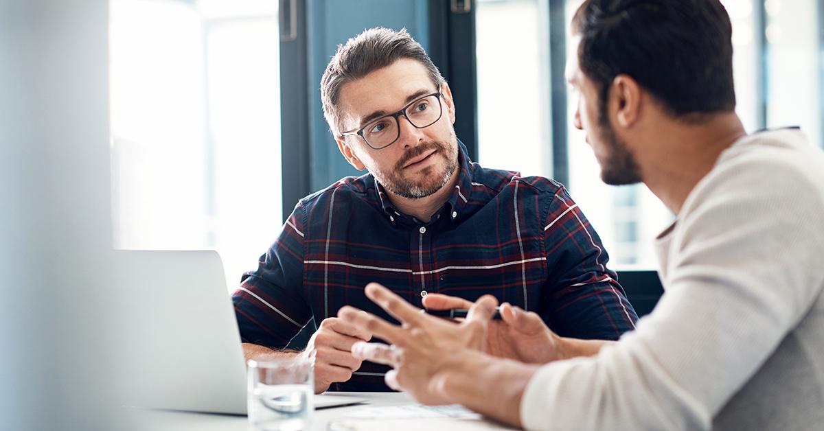 Två personer i ett coachande samtal på arbetsplatsen.